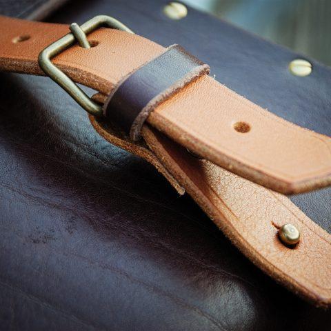 détail de la sangle de fermeture de la sacoche cuir et bois