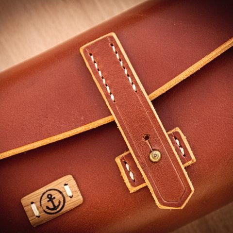 sac à main cuir et bois detail du logo et de la couture à la main point sellier